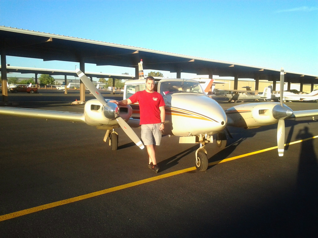A guy wearing a red shirt next to a small aircraft..