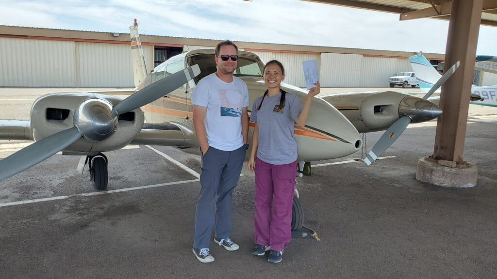 An instructor with his female student smiling in front of a plane.