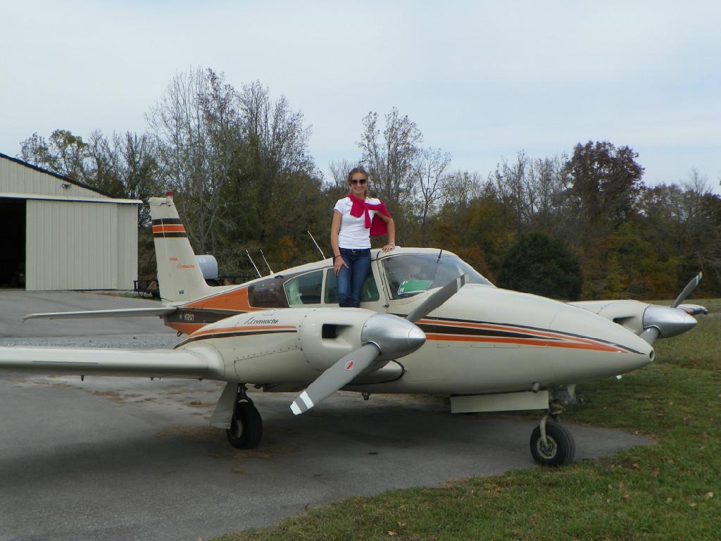 A woman wearing a white shirt standing on a plane.