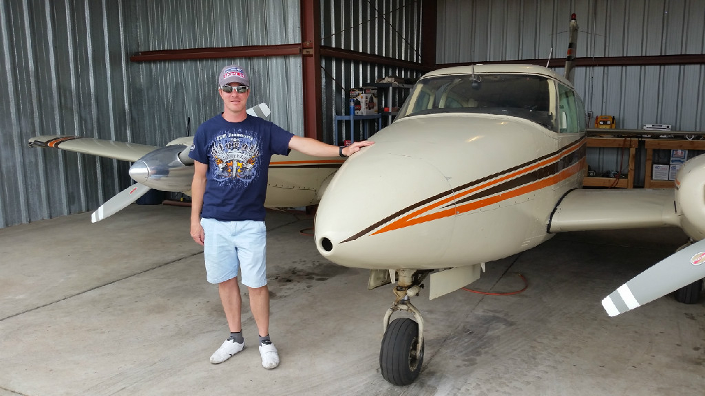A guy with a blue shirt and gray hat standing next to an airplane.