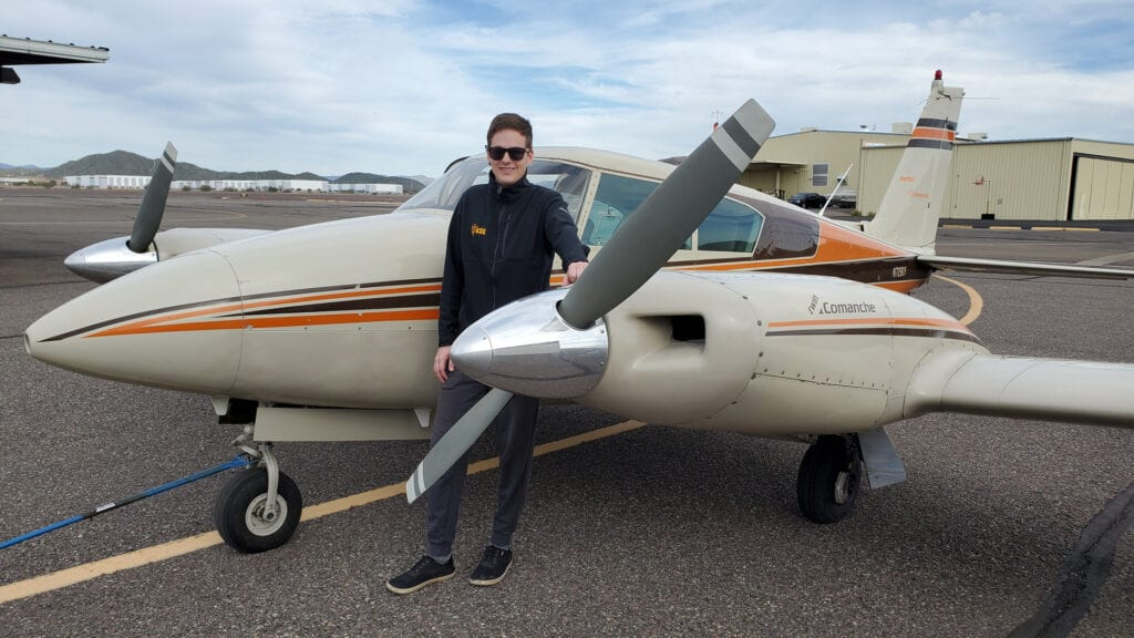 Man in a black jacket and sunglasses leaning on an aircraft.