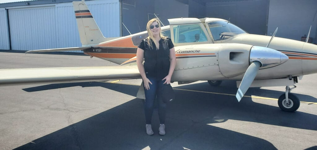 Woman in a black blouse smiling next to an aircraft.