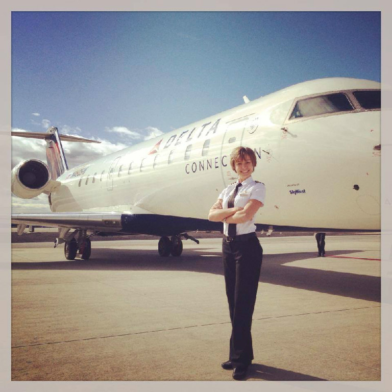 A female pilot posing in front of a Delta aircraft.