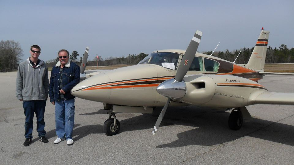 Two people smiling and standing beside each other with an airplane.