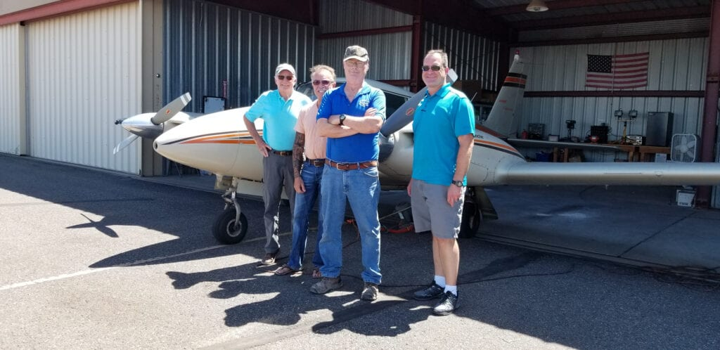 Four men posing in front of a small aircraft.