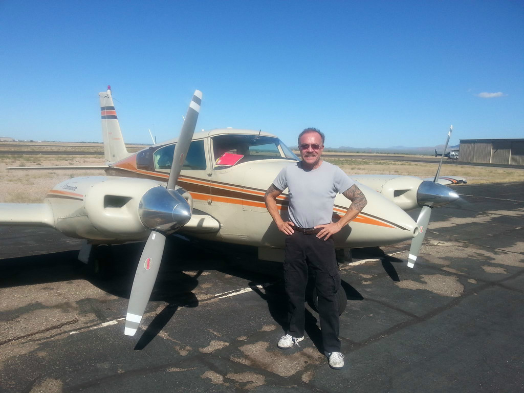 An old guy posing in front of an aircraft.