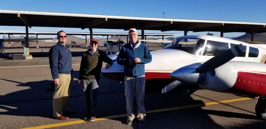 A trio of men smiling next to an airplane.