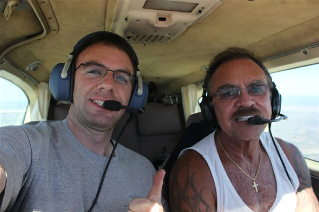 A flight instructor taking a selfie with his student.