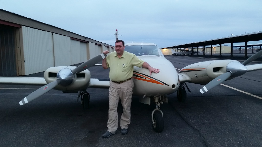 A man posing in front of a small plane.