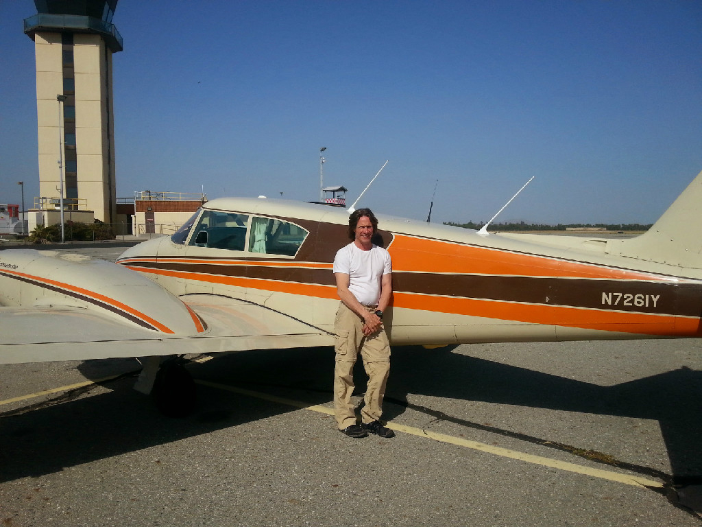 A guy leaning against a small aircraft.