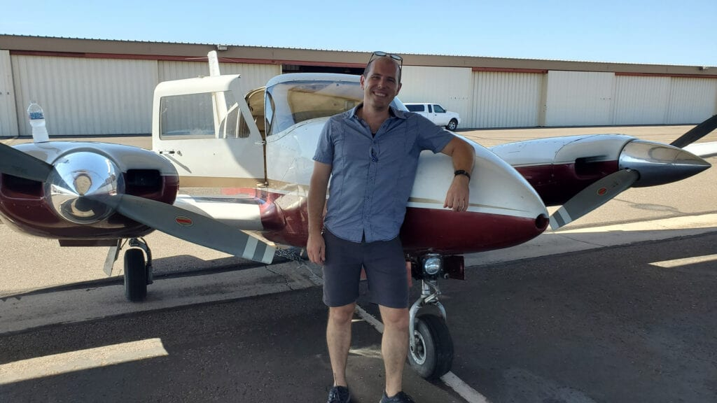 Caucasian man smiling and leaning against a plane.