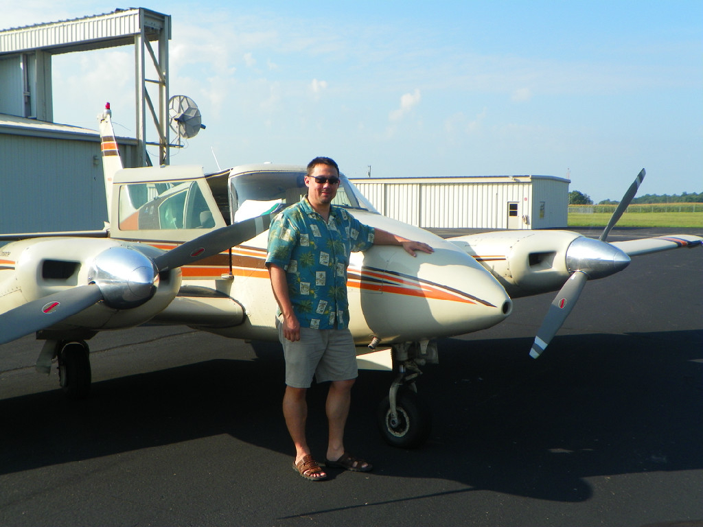 A man wearing a printed shirt posing in front of a plane.