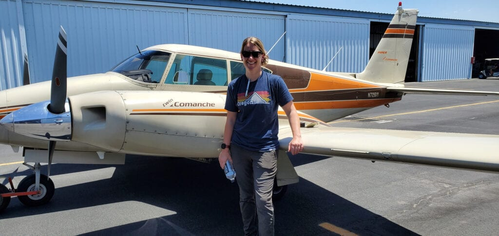 Woman in a dark blue shirt leaning on an airplane wing.