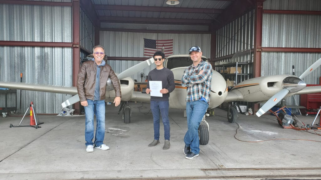Two instructors posing with their student.