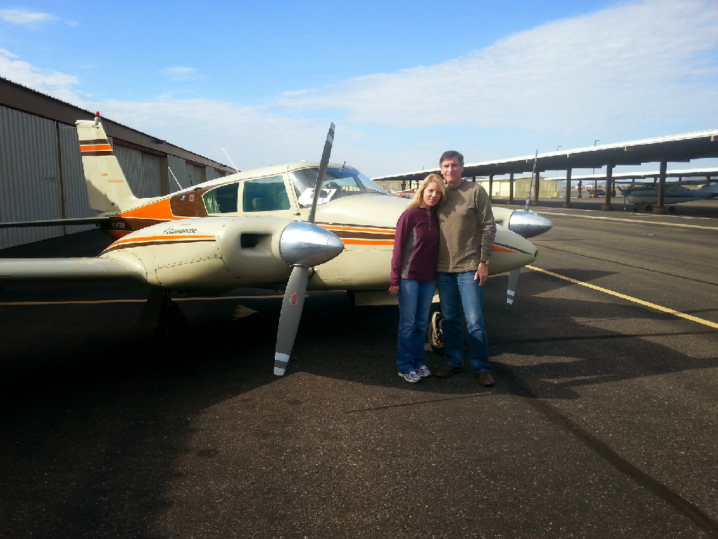 A couple standing in front of a plane.