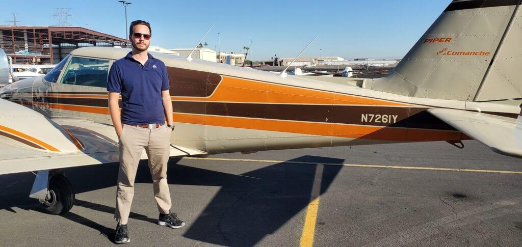 Man in a dark blue shirt next to an aircraft.