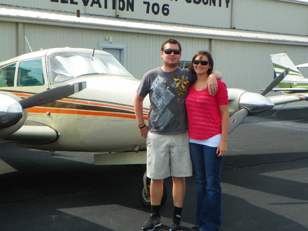 A couple posing for a photo in front of an airplane.