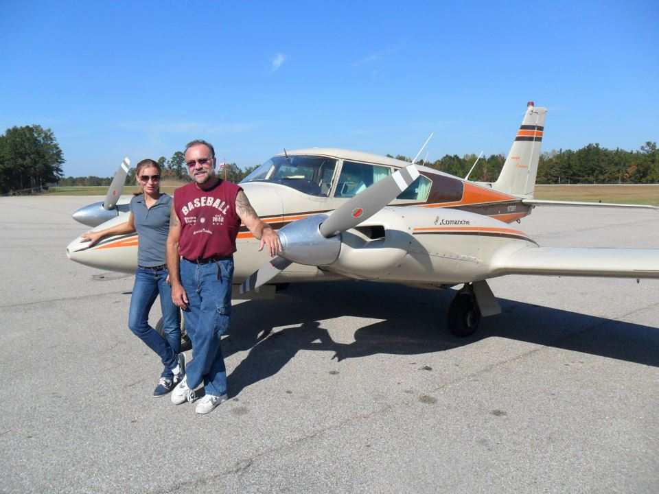 An old man and a young woman posing beside an airplane.