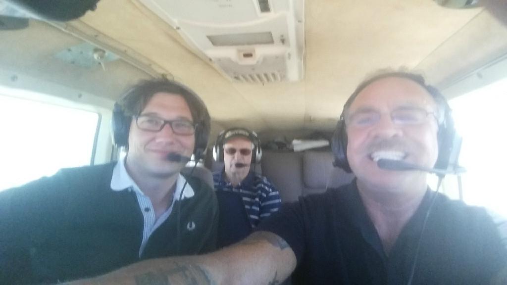 Three guys taking a photo inside an aircraft.
