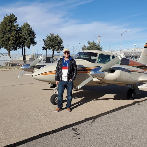 Man wearing a black jacket and dark denim pants posing in front of a plane.