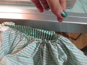 Once you've sewn all the way across the entire piece of fabric, you pull the thread from each end and it will create the gathers. You can slide the fabric back and forth across the thread to get it evenly spaced or to make it the same length as the flat piece of fabric to which it'll be attached.