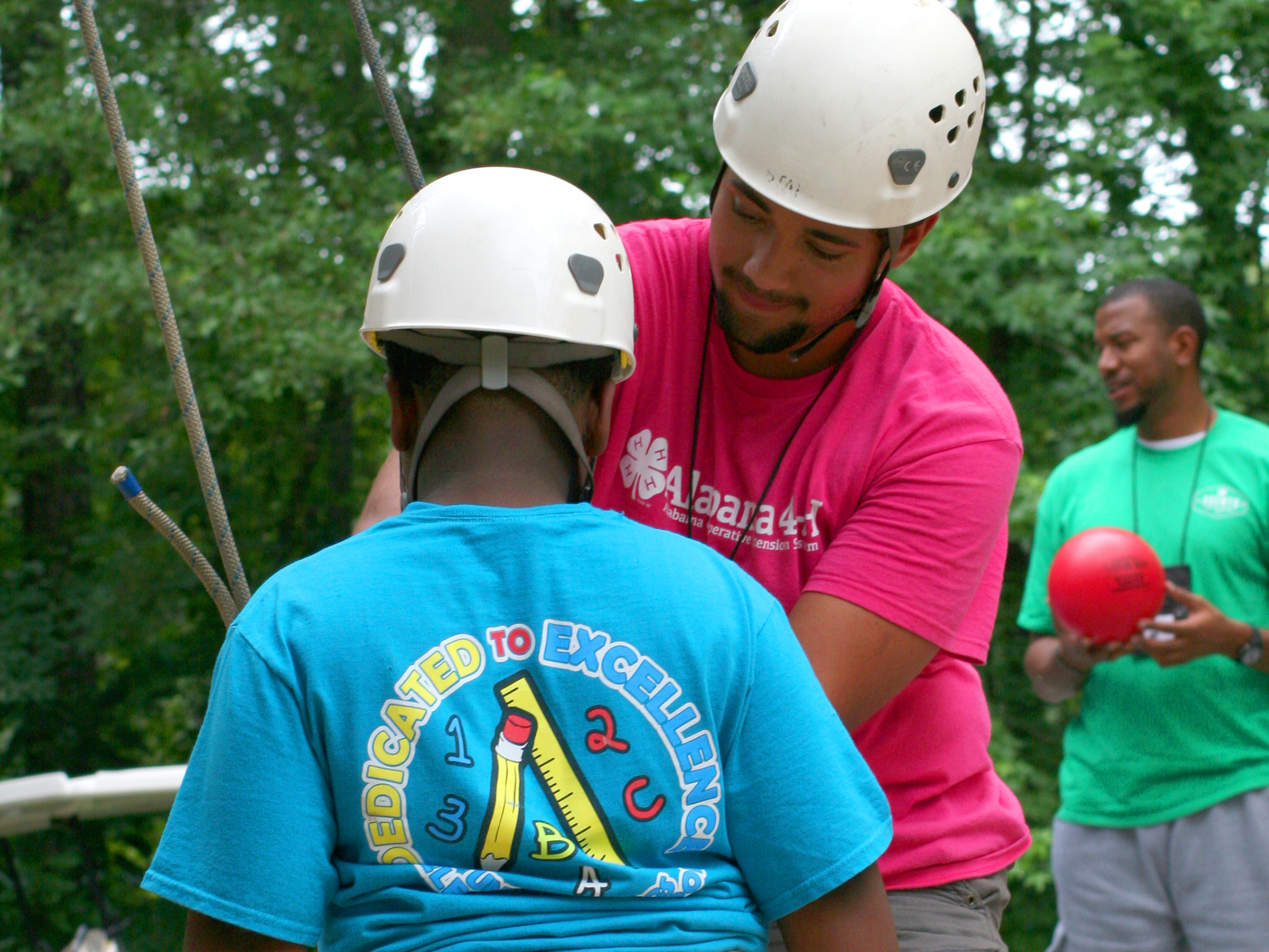 youth being assisted into a safty harness for wall climbing