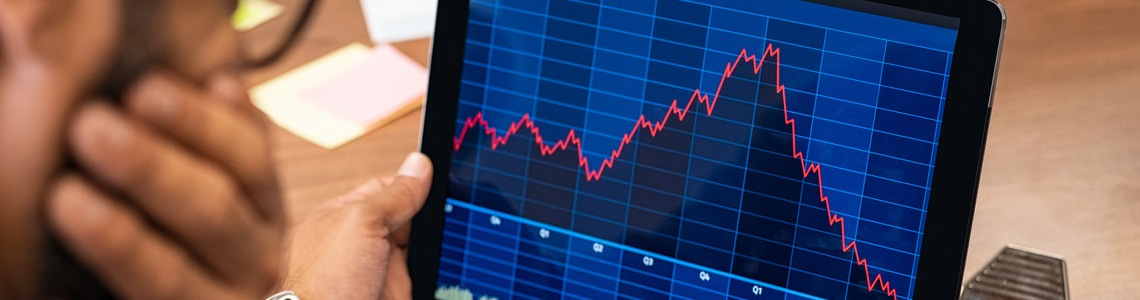 Closeup of a stock market broker working with graphs on digital tablet at office. Rear view of stock agent reading bad report and graph. Back view of multiethnic businessman analyzing fall sales.