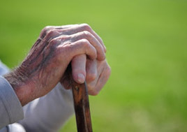 View of elderly man's hands holding cane