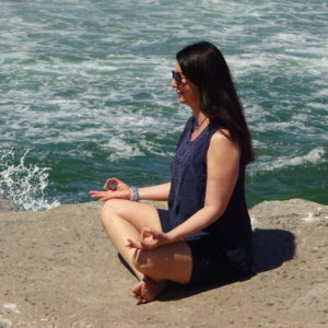 Genevieve meditates rock ocean