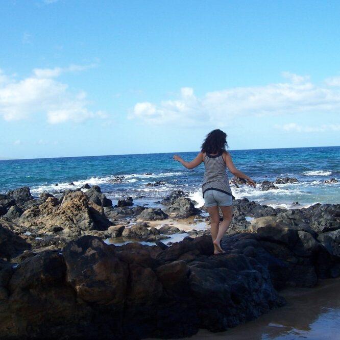 Woman walking on the rocks on the Beach in Hawaii.
