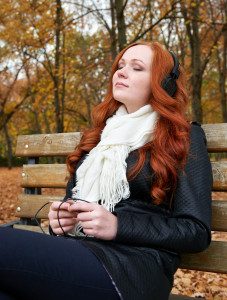 redhead girl listen music on headphones and relaxing in city park, fall season