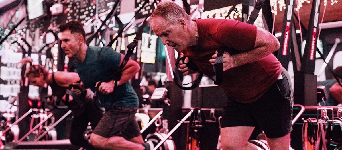 Men exercising with TRX straps