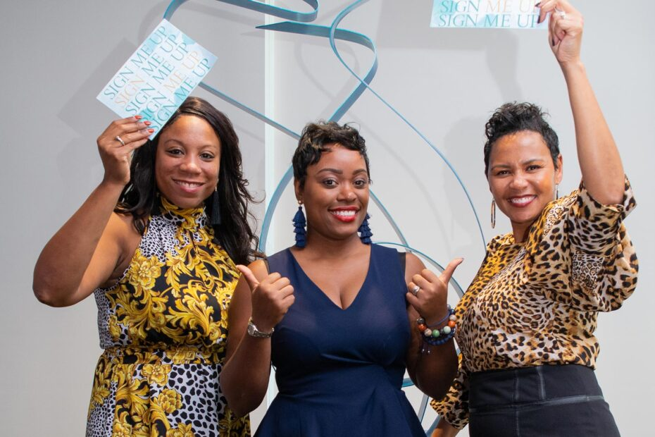"""Three smiling women holding """"sign me up"""" cards at a Women's Committee event"""