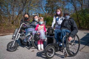 A family with people using wheelchairs poses at the be.well Halloween Hike