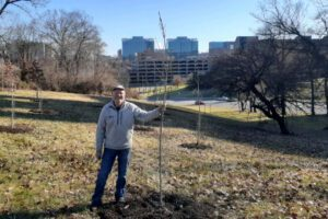 Dave Gamstetter holding a freshly planted tree