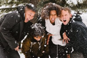 A family laughing in a snowball fight