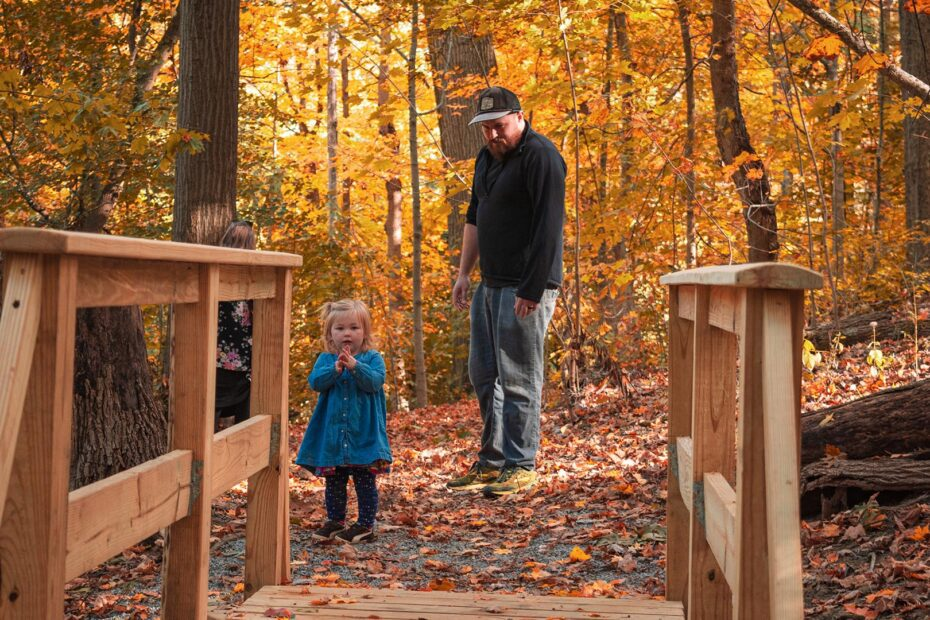 A toddler looks at a wooden bridge in a autumn forest as her father looks on.