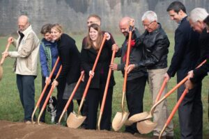 A group of people hilding shovels and smiling at a ground breaking at Tome Jones Commons