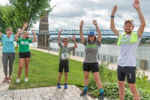A family and racer throwing their hands in the air with excitement at the be.well race at Smale Riverfront Park.