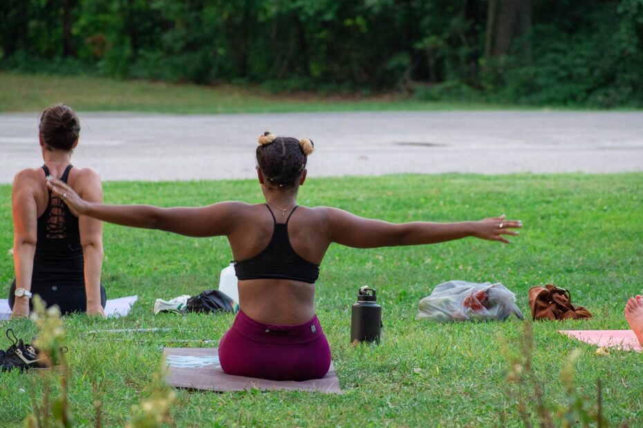 A woman with her arms outstretched, doing yoga in the park.