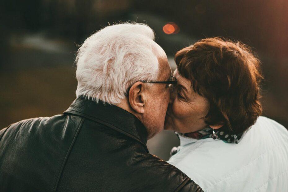 A senior couple sharing a kiss at sunset