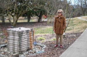 Marjorie stands by her sculpture in Eden Park