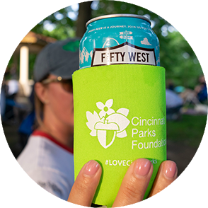 Woman holding up a beer can with an Cincinnati Parks Foundation logo on it