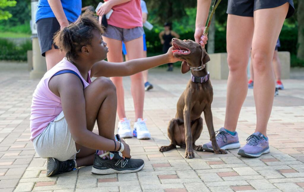 A be.well athlete petting her run buddy's dog.