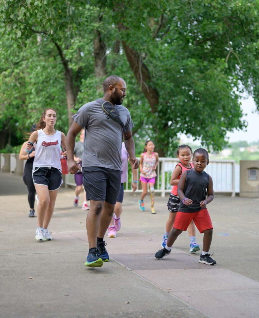 A team of athletes runs through Cincinnati Parks in the be.we;; program