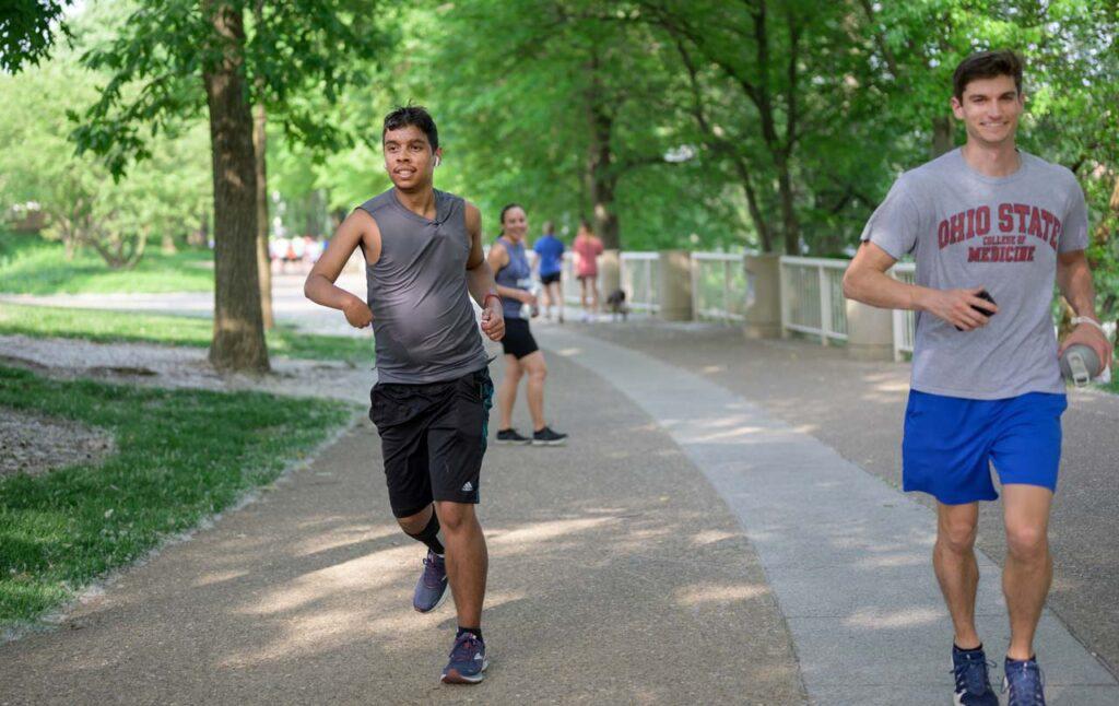 An athlete with disabilities runs through a Cincinnati Park in the be.well program.