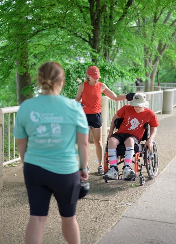Fleet Feet's Coach Katie cheers on an athlete who uses a wheelchair.