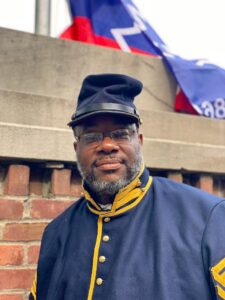 Man in uniform standing with the Juneteenth Flag in Eden Park
