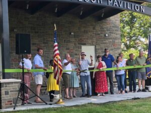 A group cutting the ribbon at the Kyle Plush Pavilion in Stanbery Park.
