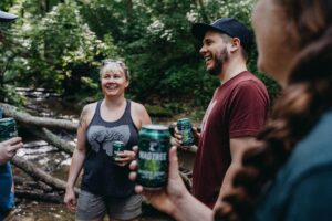 People hiking in the woods with MadTree Beer